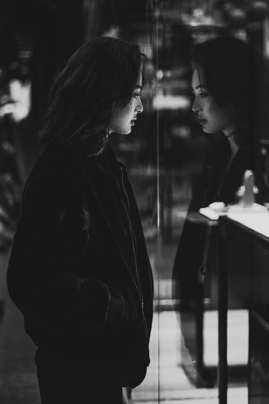 woman in black jacket standing beside mirror